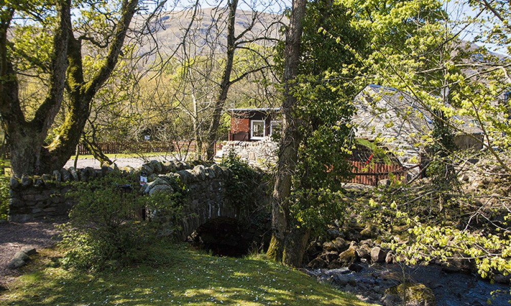 Accommodation - Luxury Lodges with Hot Tubs - Old Mill Lodge entrance over the small bridge