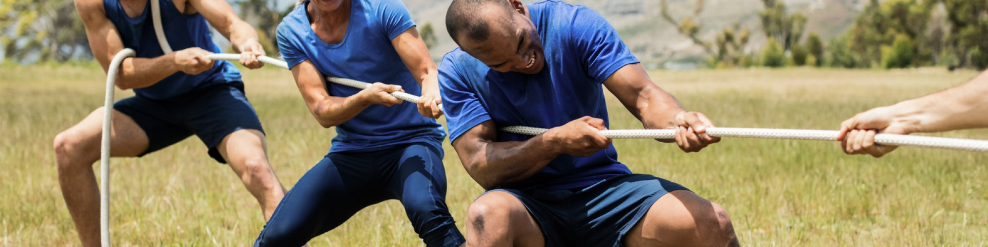 Adventures Corporate People playing tug of war during obstacle training course