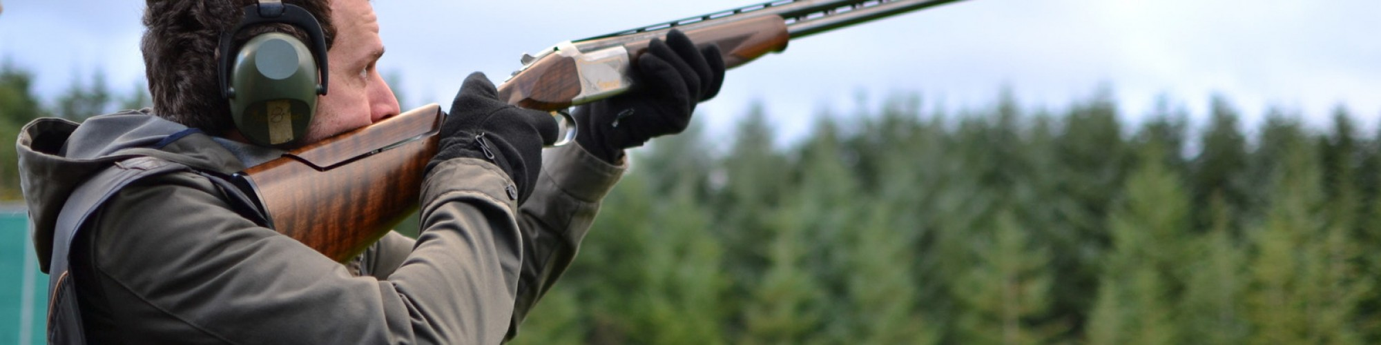 Canva man shooting shotguns at clay pigeon outdoors